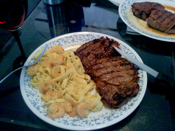 15th anniversary dinner at home, with an obscenely large ribeye steak and pasta and shrimp and wine