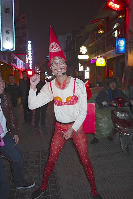 bachelor in Changsha with a painted face and wearing red women's underwear, a red hat, and Chinese flags