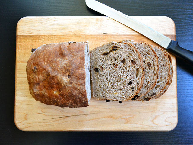 loaf of raisin spice bread with three slices cut off