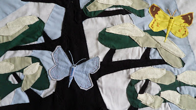 Machine appliqué with butterflies and tree. Close up of two butterflies between the leaves.