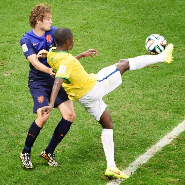 Netherlands' defender Daley Blind (L) and Brazil's midfielder Ramires vie for the ball during the third place play-off football match between Brazil and Netherlands during the 2014 FIFA World Cup at the National Stadium in Brasilia on July 12, 2014.