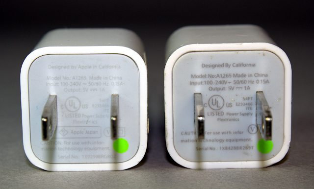 A photograph of two very similar looking chargers, with one being a genuine Apple charger and one being counterfeit.