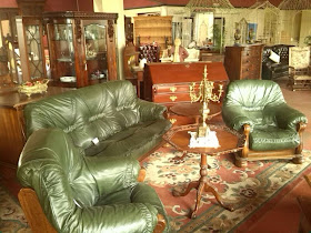 Plush padded antique upholstered suite in drawing room shop display