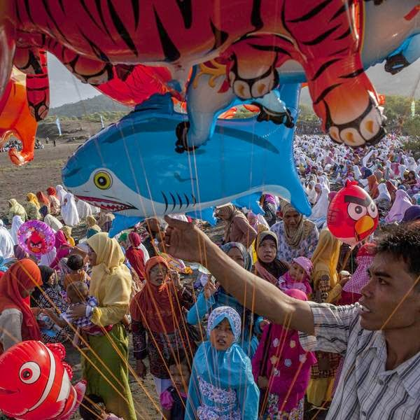 A man sells balloons as Indonesian muslims attend Eid Al-Fitr prayer on 'sea of sands' at Parangkusumo beach, in Yogyakarta, Indonesia.