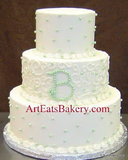 Three tier ivory butter cream wedding cake with green sugar pearls, curlicue piping and monogram