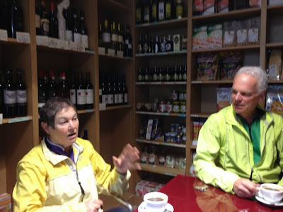 drinking coffee with shelves of wine bottles
