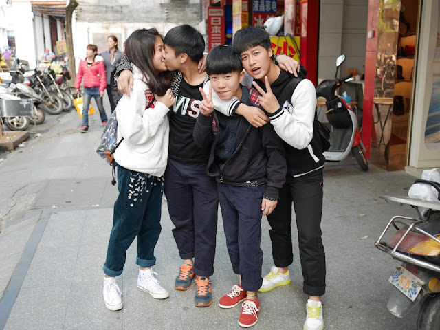 Two of four teenagers in Yangjiang, China, kiss while posing for a photo.
