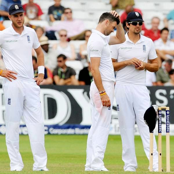 England's Stuart Broad, left, James Anderson and Alastair Cook, right, confer during day five of the first Test between England and India at Trent Bridge cricket ground, Nottingham, England, Sunday, July 13, 2014.