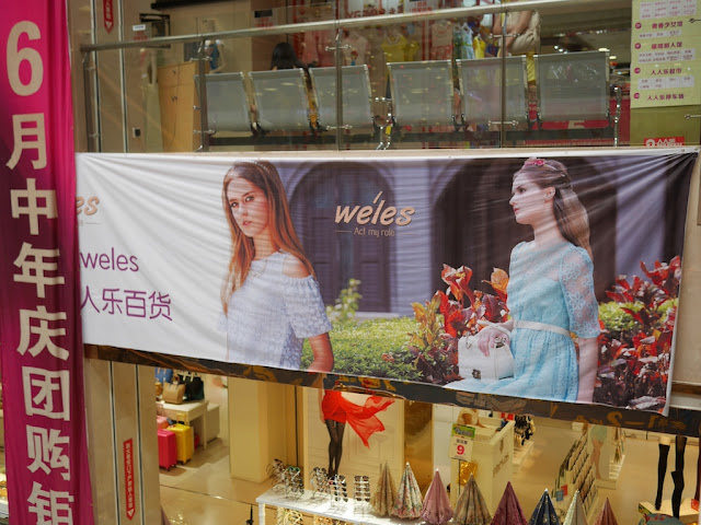 "Banner ad for Weles (威兰西) with the advertising slogan 'Act my role"" hanging inside a department store in Hengyang, China"