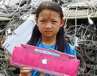 Girl in front of pile of e-waste in Guiyo, China