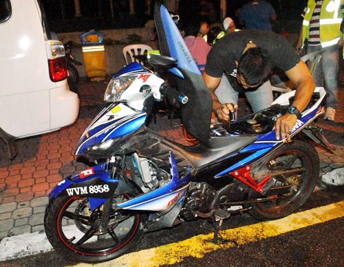 PERIKSA...anggota polis memeriksa motosikal remaja terbabit.