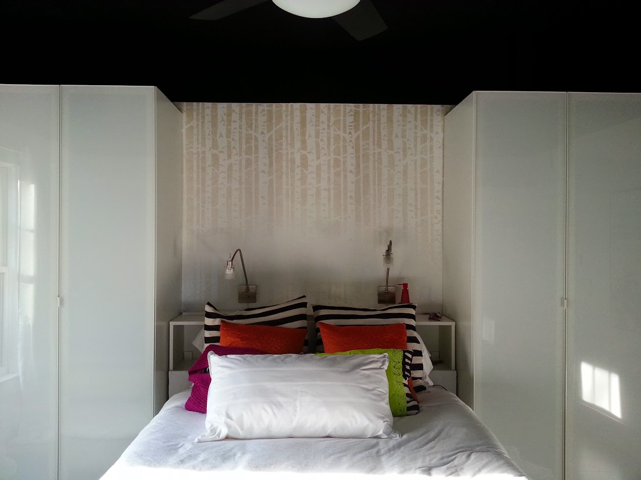 Bed, stenciled headboard wall, wardrobes