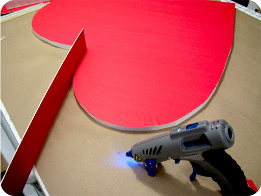 With a hot-glue gun, adhere the mat board, red side facing in, to the edge of the heart. Draw a line of glue in small lengths onto the foam board edge and hold the mat board to it until it is completely stuck.