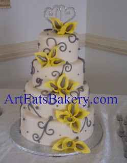 Four tier fondant wedding cake with hand made edible yellow and gray calla lily flowers, swirls, pearls and double heart topper