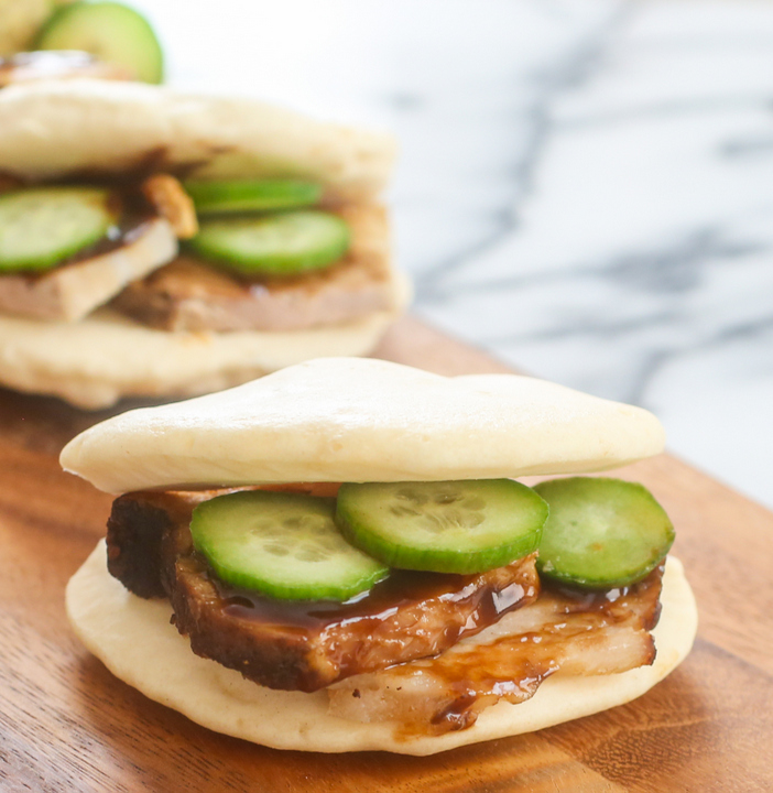 a close-up photo of chinese bun with pork, hoisin sauce, and cucumber slices