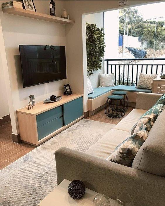 Sala com varanda pequena, sofá cinza, com almofadas coloridas e hack de madeira com objetios decorativos.