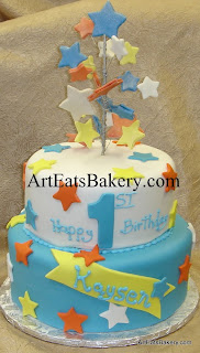 Two tier boy's 1st birthday cake with white, blue, yellow and orange stars and star topper