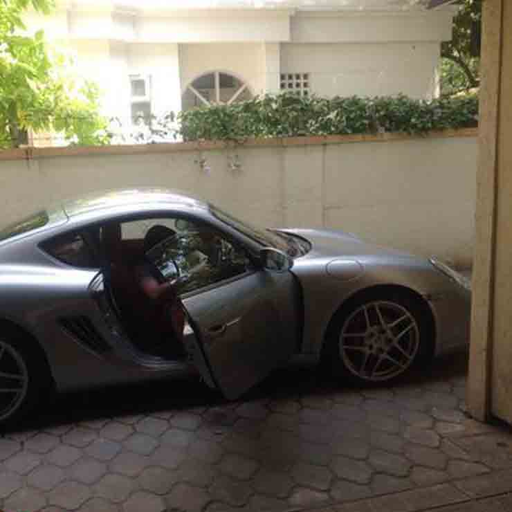 Dinesh Karthik getting out of his porsche cayman S