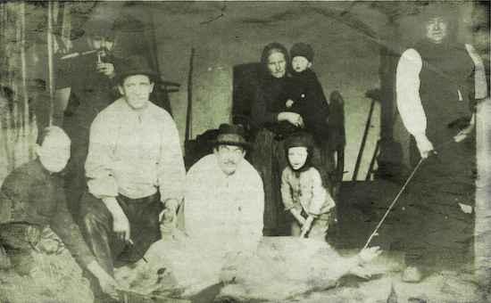 """Hausschlachtung im Jahre 1904 auf der Deele des Hauses Budde in Schlangen. Hausschlachter ist Fritz Vollmer (3. von links). Willi Budde hält den """"Stert"""" und Wilhelm Budde den Strick. Foto: Budde"""