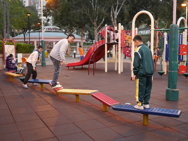 people playing on a row of wobbly connected planks at Fung Tak Park in Wong Tai Sin, Hong Kong