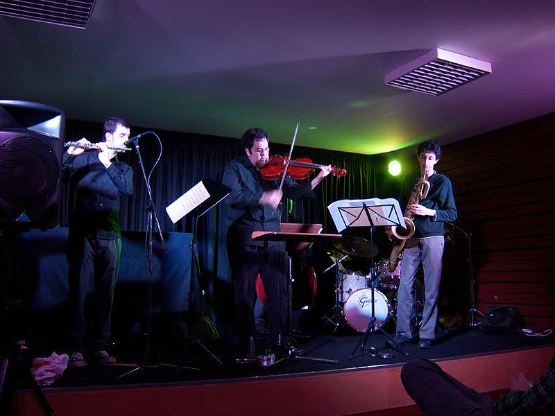 Vista alargada do palco, com José valente ao centro. o flautista à esquerda e o saxofonista à direita