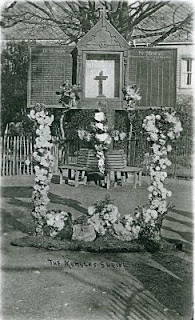 The Shrine, made of wood and painted black is shown here resplendent with wreaths and flowers.