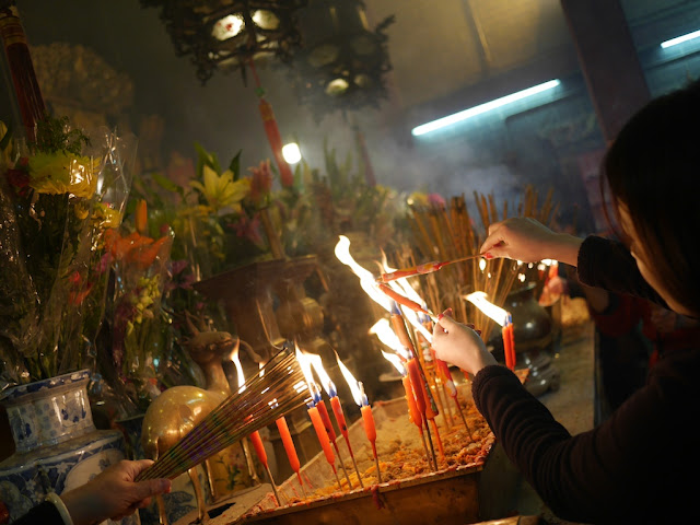 people lighting incense sticks in Kwun Yum Temple