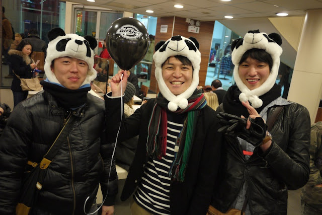 Japanese guys wearing panda hats and holding a Dickies balloon
