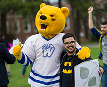 Image of mascot with student