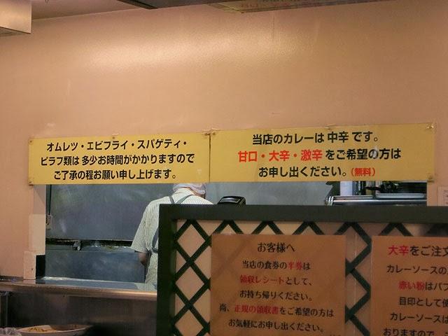 壁に書かれた辛さの案内と料理提供時間の案内