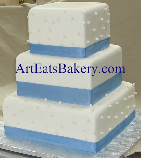 Three tier square white fondant unique wedding cake design idea with edible sugar pearls and blue ribbons