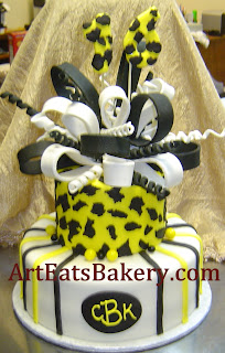 Two tier yellow, black and white custom leopard and stripe 16th birthday cake design with sugar bow and monogram