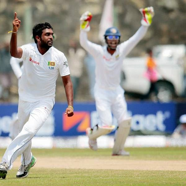 Sri Lankan bowler Dilruwan Perera, center, celebrates taking the wicket of South African batsman Alviro Petersen, left, during the fourth day of the first test cricket mach between them in Galle, Sri Lanka, Saturday, July 19, 2014.