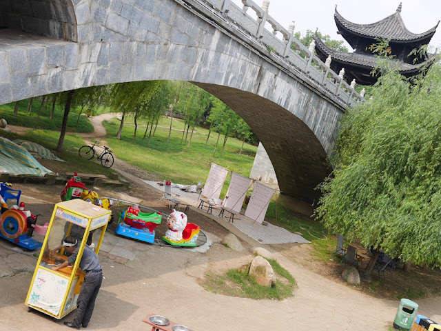 circular kiddie train and area for shooting balloons under a traditional Chinese style bridge