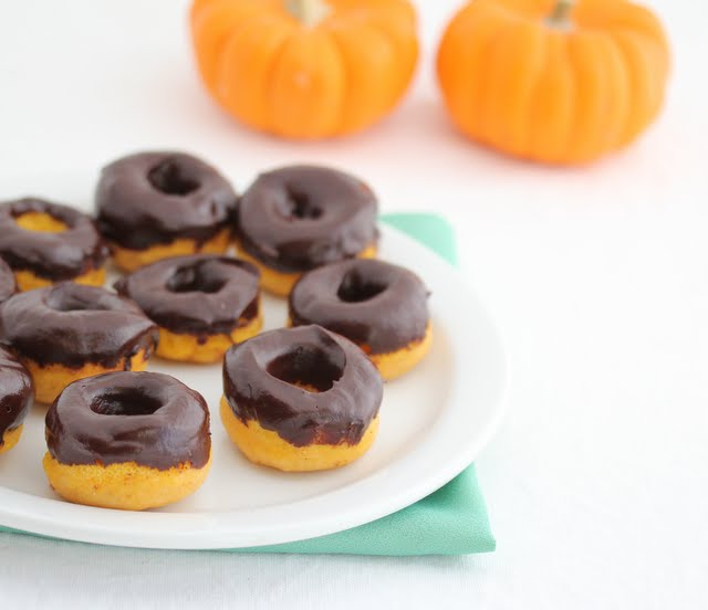 photo of chocolate glazed mini donuts on a plate with small pumpkins in the background