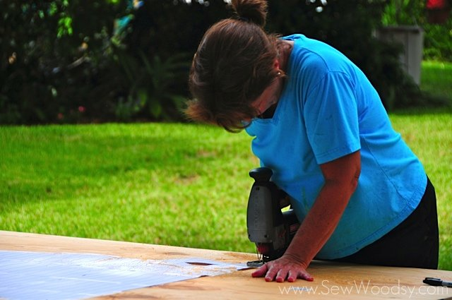 Woman using a jigsaw cutting around a paper template on plywood.
