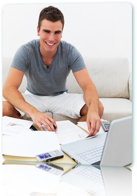 Smiling man doing paperwork, using a computer.