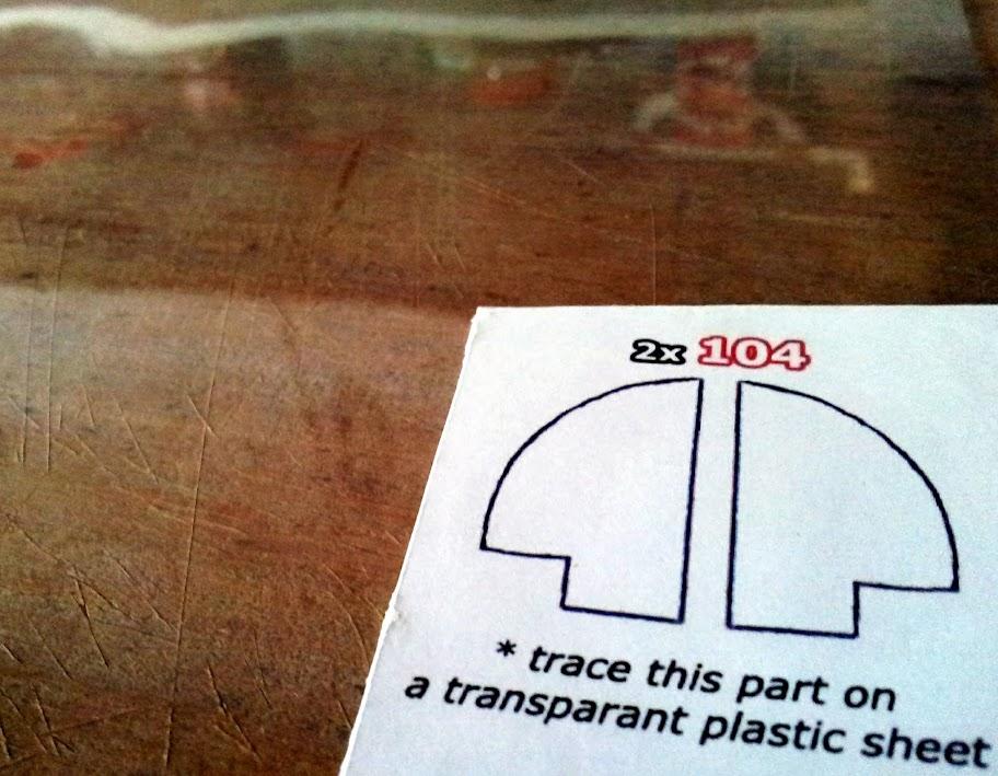 Pegamos como hicimos con el frente, las partes transparentes de la escotilla, en acetato, por fuera de las líneas de corte.