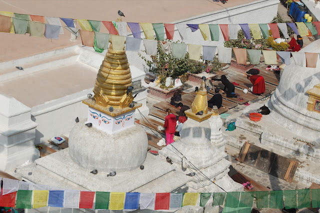 Buddhist practitioners, surrounded by small stupas, doing prostrations on wooden boards on the first terrace of the Boudhanath stupa