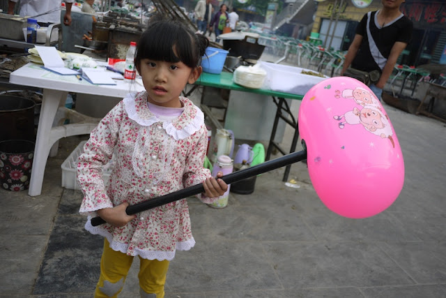 little girl holding a large inflatable hammer in Zhongwei, Ningxia, China