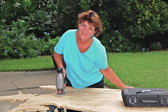 Woman smiling cutting with a jigsaw on plywood.