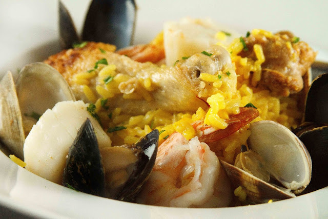 close up of paella in a white bowl