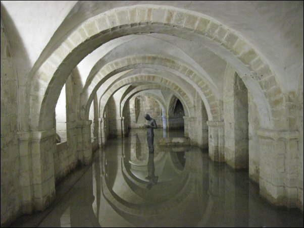 A statue gazes down at its cupped hands. It is reflected in the low surrounding water