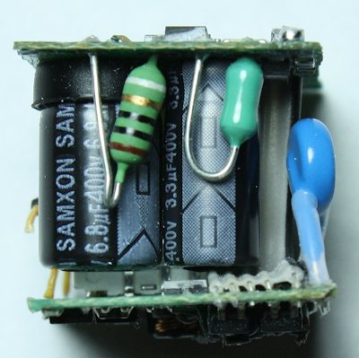 Apple iPhone charger, showing the fusible resistor (striped), inductor (green) and Y capacitor (blue). The two electrolytic filter capacitors are behind (black)