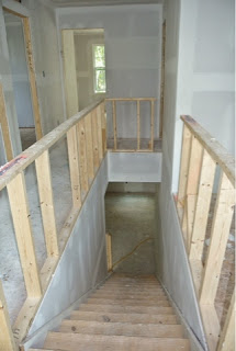 Picture of the stairway between first and second floors just after drywall installed