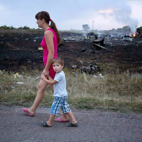 A woman with a child walks past the crash site of a passenger plane near the village of Grabovo, Ukraine, Thursday, July 17, 2014.