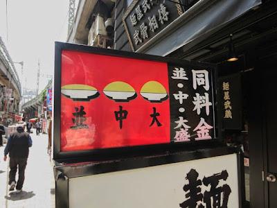店頭の立看板に書かれた、麺大盛り同料金の案内