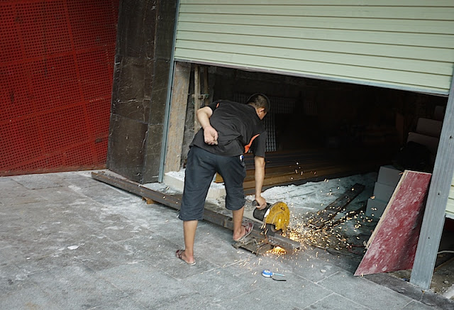 man cutting metal without any safety equipment in Shenzhen, China
