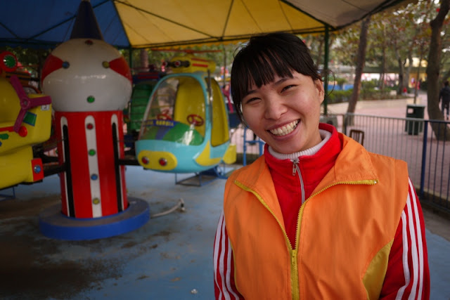 Young worker standing in front of a helicopter amusement park ride in Zhuhai, China