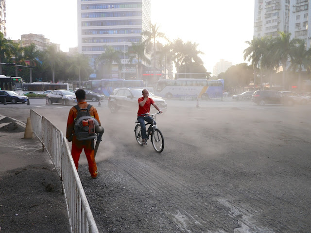 man covering his mouth with his hand while riding a bike through a dust cloud created by a gravelblower